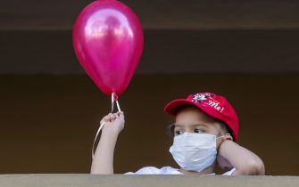 """TOPSHOT - A patient with cancer holds a balloon prior to the """"March of the Balloons"""", an activity that is carried out for the International Day of the Fight Against Childhood Cancer, in Managua, on February 17, 2018.About 250 new cases of children with cancer are diagnosed each year in Nicaragua and more than 70 percent of them survive after being treated, according to data from the Association of Mothers and Parents of Children with Leukemia and Cancer (Mapanica). / AFP PHOTO / INTI OCON        (Photo credit should read INTI OCON/AFP via Getty Images)"""