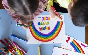"""MILAN, ITALY - MARCH 13:  Children draw a rainbow and the slogan of hope being shared in Italy """"Andrà tutto bene."""" (Everything will be alright.) during quarantine measures amid the novel coronavirus COVID-19 pandemic on March 13, 2020 in Milan, Italy. Italy, which has seen the worst COVID-19 outbreak outside of China, tightened quarantine restrictions on Thursday, closing all commercial activities except supermarkets, pharmacies and banks.  (Photo by Pietro D'Aprano/Getty Images)"""