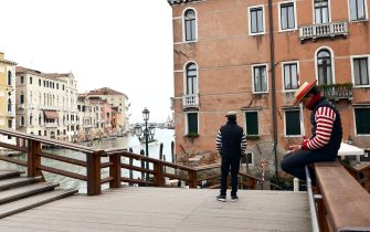 A Gondoliere checks his mobile phone as another waits for tourists in Venice on March 5, 2020. - Italy closed all schools and universities until March 15 to help combat the spread of the novel coronavirus crisis. The government decision was announced moments after health officials said the death toll from COVID-19 had jumped to 107 and the number of cases had passed 3,000. (Photo by ANDREA PATTARO / AFP) (Photo by ANDREA PATTARO/AFP via Getty Images)