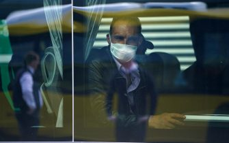 SCHOENEFELD, GERMANY - APRIL 09: A seasonal worker from Romania wears a protective mask as he sits in a bus after arriving with others on a chartered flight at Schoenefeld Airport during the coronavirus crisis on April 09, 2020 in Schoenefeld, Germany. The German government initially imposed a ban on seasonal workers coming from abroad as part of measures to stem the spread of the coronavirus. The restriction was recently relaxed and workers are now arriving on special flights and undergo health checks upon their arrival. The labor-intensive asparagus harvest depends heavily on workers from Romania and Poland. (Photo by Sean Gallup/Getty Images)