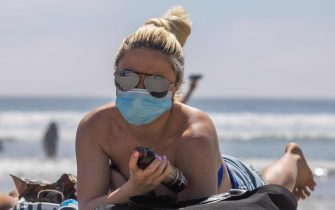 A woman wearing a face mask sunbathes on the beach amid the novel coronavirus pandemic in Huntington Beach, California on April 25, 2020. - Orange County is the only county in the area where beaches remain open, lifeguards in Huntington Beach expect tens of thousands of people to flock the beach this weekend due to the heat wave. Lifeguards and law enforcement are patrolling the beach to make sure people are keeping their distance. (Photo by Apu GOMES / AFP)