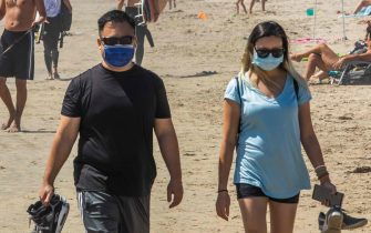 People walk on the beach, some wearing masks, amid the novel coronavirus pandemic in Huntington Beach, California on April 25, 2020. - Orange County is the only county in the area where beaches remain open, lifeguards in Huntington Beach expect tens of thousands of people to flock the beach this weekend due to the heat wave. Lifeguards and law enforcement are patrolling the beach to make sure people are keeping their distance. (Photo by Apu GOMES / AFP)