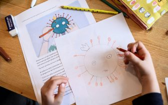 A child draws a COVID-19 coronavirus as part of school homeworks on March 12, 2020 in Manta, near Cuneo, Northwestern Italy, as Italy shut all stores except for pharmacies and food shops in a desperate bid to halt the spread of a coronavirus that has killed 827 in the the country in just over two weeks. (Photo by MARCO BERTORELLO / AFP) (Photo by MARCO BERTORELLO/AFP via Getty Images)