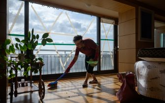 A woman cleans an apartment after strong winds from Typhoon Maysak left windows shattered, near Gwangalli beach in Busan on September 3, 2020. - At least one person was killed and more than 2,000 people evacuated to temporary shelters in South Korea as a powerful typhoon churned across the peninsula, authorities said. (Photo by Ed JONES / AFP) (Photo by ED JONES/AFP via Getty Images)