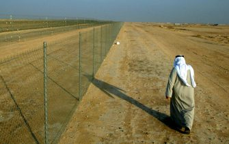 ON NORTHERN BORDER BETWEEN IRAQ AND KUWAIT, KUWAIT - JANUARY 22:  A Kuwaiti man walks along the border fence that separates Kuwait from Iraq on the northern border January 22, 2003 in Kuwait. The United Nations continuously monitors the border region.  (Photo by Joe Raedle/Getty Images)