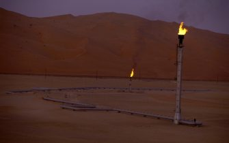"SHAYBAH, SAUDI ARABIA - MARCH 2003:  Flare stacks burn at the Saudi Aramco oil field complex facilities at Shaybah in the Rub' al Khali (""empty quarter"") desert on March 2003 in Shaybah, Saudi Arabia. (Photo by Reza/Getty Images)"