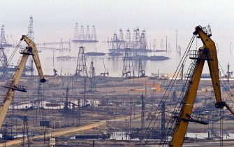 BAKU, AZERBAIJAN:  Oil towers sprout in the oil-rich Caspian sea  near the capital Baku, 19 October 2003. Ilham Aliyev, son of ailing former Azerbaijan president Haydar Aliyev, won the presidential election this week to replace his father in power in this oil- rich former Soviet republic.Ilham Aliyev has vowed to follow the policies of his father Haydar Aliyev, the dominant force in the Caspian state since 1960s.  AFP PHOTO / TARIK TINAZAY  (Photo credit should read TARIK TINAZAY/AFP via Getty Images)