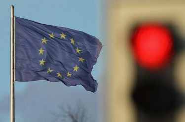 BERLIN, GERMANY - NOVEMBER 30:  A flag of the European Union waves in the wind near a traffic light showing red on November 30, 2011 in Berlin, Germany. Many European leaders are warning that the growing debt crisis within the Eurozone is reaching critical proportions and that only weeks remain to take decisive action if the Euro is to survive.  (Photo by Sean Gallup/Getty Images)
