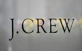The J.Crew logo is seen at the window of a closed J.Crew store near Rockefeller Plaza on May 4, 2020 in New York City. - US clothing retailer J. Crew filed to begin bankruptcy protection proceedings Monday, after reaching an agreement with major creditors on a $1.65 billion debt restructuring plan, the company said in a statement. The brand, whose clothes have been worn by former first lady Michelle Obama, said online sales operations, which account for more than half its revenues, will continue as normal. (Photo by Angela Weiss / AFP) (Photo by ANGELA WEISS/AFP via Getty Images)