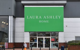 A shopper passes the front entrance of the Laura Ashley womenswear and homewear store in Aintree, Liverpool, north-west England on March 17, 2020. - British clothing and household goods retailer Laura Ashley Holdings collapsed Tuesday, March 17 into administration as rescue talks failed due to coronavirus turmoil, risking up to 2,700 jobs. (Photo by Paul ELLIS / AFP) (Photo by PAUL ELLIS/AFP via Getty Images)