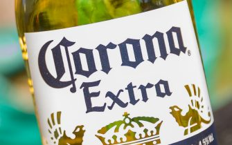 BOCHUM, GERMANY - APRIL 25: (BILD ZEITUNG OUT) The logo and lettering of the Mexican brewery Corona on a beer bottle label is seen on April 25, 2020 in Bochum, Germany. (Photo by Mario Hommes/DeFodi Images via Getty Images)