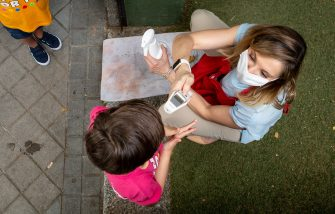 MADRID, SPAIN - JUNE 24: A child has her temperature checked by a member of staff before entering English For Fun school on June 24, 2020 in Madrid, Spain. English For Fun is a private school that works with preschool children (aged 1 to 6 years old) as well as enrichment classes for pre-teens (aged 7 â   14 years old). They have been offering online classes to support families during lockdown, and after restrictions were eased and the spread of Coronavirus declined, they opened their doors on Monday 22nd offering Urban Summer Camps for kids. With the end of the state of alarm, the Government has announced that pre-schools can reopen from July 1st, but only as an option for parents that can't work from home, so many parents are using alternatives like private Urban Summer Camps like English for Fun as a solution. The school's staff have put into place many safety measures, such as regular supervised handwashing, temperature checks on arrival, regular ventilation of classrooms and enhanced cleaning regimes to keep pupils and staff as safe as possible. (Photo by Pablo Cuadra/Getty Images)