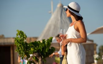 """MARSALA, ITALY - JULY 30: A tourist holds a glass of wine at Salina Genna on July 30, 2020 in Marsala, Italy. On the west coast of Sicily, between Trapani and Marsala, along the so-called """"Way of the salt"""", there are still a few marine salt cultivations producing salt from sea water using ancient techniques. The salt flats have become nature reserves and they are now a destination for tourists from all over the world. (Photo by Tullio Puglia/Getty Images)"""