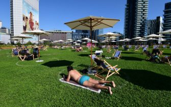 """People sunbathe in a kind of green beach amid the skyscrapers called """"Il Lido Bam"""" located in the """"Library trees"""" park on June 23, 2020 in the Porta Nuova district, center Milan. (Photo by Miguel MEDINA / AFP) (Photo by MIGUEL MEDINA/AFP via Getty Images)"""