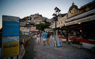 A view taken as the sun sets on June 30, 2020 shows people walk along the Positano beachfront on the Amalfi coast in southern Italy. - With its white and multicoloured houses perched on the mountainside about the crystalline waters of the Mediterranean, Italy's Amalfi coast is suffering from this year's lack of US tourists. (Photo by Filippo MONTEFORTE / AFP) (Photo by FILIPPO MONTEFORTE/AFP via Getty Images)