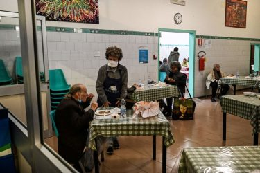 TOPSHOT - Persons in need eat lunch served at the canteen of lay Catholic Community of Sant'Egidio dedicated to social service in Rome, on April 13, 2020 during the country's lockdown aimed at curbing the spread of the COVID-19 infection, caused by the novel coronavirus. (Photo by Vincenzo PINTO / AFP) (Photo by VINCENZO PINTO/AFP via Getty Images)