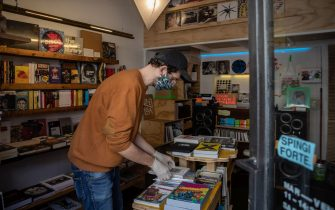 MILAN, ITALY - MAY 06: A bookseller, wearing protective gloves and a face mask, works inside 'Volume' independent bookstore, located in the Isola district on May 06, 2020 in Milan, Italy. Italy was the first country to impose a nationwide lockdown to stem the transmission of the Coronavirus (Covid-19), and its restaurants, theaters and many other businesses remain closed. (Photo by Emanuele Cremaschi/Getty Images)