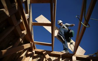 PETALUMA, CA - JANUARY 21:  A worker carries lumber as he builds a new home on January 21, 2015 in Petaluma, California. According to a Commerce Department report, construction of new homes increased 4.4 percent in December, pushing building of new homes to the highest level in nine years. (Photo by Justin Sullivan/Getty Images)