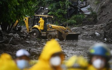 Rescuers and firefighters search for seven people who were buried by a landslide caused by Tropical Storm Cristobal, in Santo Tomas, El Salvador, on June 3, 2020. - Tropical Storm Cristobal's formation in the Gulf of Mexico marked a new record as the earliest that the Atlantic hurricane season has seen its third named disturbance, US meteorologists said Tuesday. (Photo by Marvin RECINOS / AFP) (Photo by MARVIN RECINOS/AFP via Getty Images)