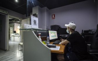 MADRID, SPAIN - JUNE 13: A member of Zoom Club is seen checking the laptop on June 13, 2020 in Madrid, Spain. Zoom Club is a Cannabis Association in Madrid made up of 500 members. As a result of the COVID-19 pandemic the facility was closed from March 15, 2020. After this period, with Madrid moving forward to phase 2, they reopened its facilities with sanitary security measures. Due to these measures, the maximum capacity has been reduced from 60 to 8 people. The members must observe sanitary rules while using the facilities, such as, wearing a mask while they are in the club, that can be taken off while smoking. Shoes soles must be sanitized, and hands cleaned with hydroalcoholic gel upon entering. Members must keep 2 meters distance from each other and can only stay indoors for a maximum of 20 minutes. They cannot use the toilets and must be placed around the dispensary without being able to use the rest of the common areas. Metraquilate screens have been placed on the counters to protect workers who are also equipped with gloves and masks to serve members.  (Photo by Alberto Ortega/Getty Images)