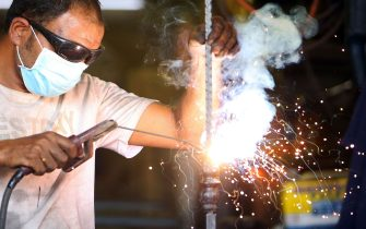 An Arab blacksmith works at a workshop in Kuwait City on September 10, 2020. - Tens of thousands of foreign workers will be forced to leave the oil-rich emirate, hard hit by collapsing crude prices, as economic woes and coronavirus stoke anti-foreigner sentiment. The cash-strapped government said last month that from January it will no longer renew work permits for expatriates over the age of 60 without university degrees. (Photo by YASSER AL-ZAYYAT / AFP) (Photo by YASSER AL-ZAYYAT/AFP via Getty Images)