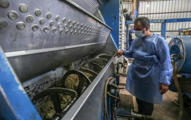 A worker watches as olives are crushed inside a machine at an olive oil factory in Khan Yunis, in the southern Gaza Strip on October 4, 2020. (Photo by SAID KHATIB / AFP) (Photo by SAID KHATIB/AFP via Getty Images)