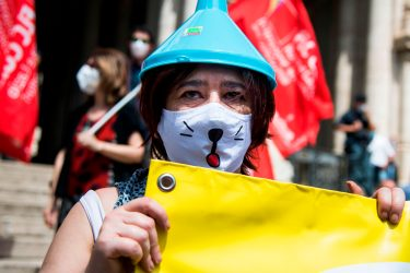 A woman wearing a funnel on her head holds a banner during a demonstration of major teachers' trade unions in front of the Ministry of Education on June 8, 2020 in Rome, as the country eases its lockdown aimed at curbing the spread of the COVID-19 infection, caused by the novel coronavirus. - Unions were holding a protest over the consequences of the coronavirus pandemic, asking for an increase in the number of teaching staff and management resources, secure buildings and the renewal of contracts for precarious workers. (Photo by Tiziana FABI / AFP) (Photo by TIZIANA FABI/AFP via Getty Images)