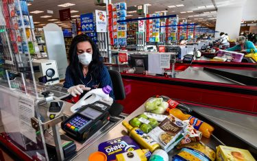 Italian cashier Valentina Pome works at an Esselunga supermarket in Milan's Famagosta district on April 30, 2020, during the country's lockdown aimed at curbing the spread of the COVID-19 infection, caused by the novel coronavirus. (Photo by Miguel MEDINA / AFP) (Photo by MIGUEL MEDINA/AFP via Getty Images)