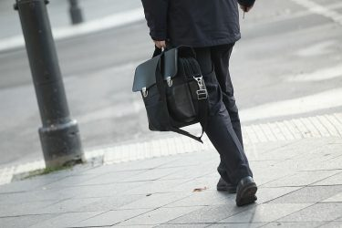 BERLIN, GERMANY - OCTOBER 12:  A man carrying a briefcase walks along Unter den Linden avenue in Mitte district on October 12, 2011 in Berlin, Germany. Mitte district is home not only to the Bundestag and the offices of Germany's lawmakers, but also to many of the corporate representations, public relations agencies, law offices and industry associations that make up the myriad league of German lobbyists who seek to influence the course of German governmental policies. In Germany many lobbyists sit on government ministerial committees and have a direct hand in drafting government legislation.  (Photo by Sean Gallup/Getty Images)