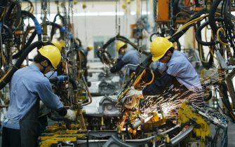 """HAIKOU, CHINA - APRIL 6:  (CHINA OUT)  Employees on the assembly line produce cars in Mazda's """"Family"""" line of vehicles at China First Automobile Works (FAW) Group Haima Automobile Co., Ltd. April 6, 2005 in Haikou, Hainan Province, China. China has become the world's third largest automotive market with 2004 car sales in the country growing 15.17 percent to 2.33 million units, even though curbs on credit reduced demand. The market began slowing by mid-2004, affected by the government's measures to cool a fast-expanding economy. Analysts expect car sales in China to increase in 2005 by 10 percent.  (Photo by China Photos/Getty Images)"""