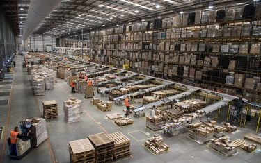 """Workers prepare customer orders for dispatch as they work around goods stored inside an Amazon.co.uk fulfillment centre in Peterborough, central England, on November 15, 2017. - Shops could be seeing the effect of consumers postponing purchases until """"Black Friday"""" on November 24, 2017, a day of sales in the United States that has become increasingly popular in Britain. (Photo by CHRIS J RATCLIFFE / AFP)        (Photo credit should read CHRIS J RATCLIFFE/AFP via Getty Images)"""