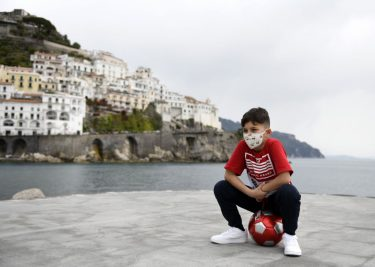 AMALFI, ITALY - MAY 13: A boy with a mask against covid 19 infection plays football at Amalfi's port on May 13, 2020 in Amalfi, Italy. Italy was the first country to impose a nationwide lockdown to stem the transmission of the Coronavirus (Covid-19), and its restaurants, theaters and many other businesses remain closed. (Photo by Francesco Pecoraro/Getty Images)
