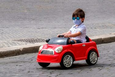 TOPSHOT - A boy wearing a face mask drives a toy car across Piazza Navona in Rome on May 28, 2020 as the country eases its lockdown aimed at curbing the spread of the COVID-19 infection, caused by the novel coronavirus. (Photo by Andreas SOLARO / AFP) (Photo by ANDREAS SOLARO/AFP via Getty Images)
