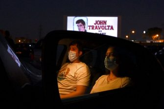 """Cinema-goers in their cars attend the screening of the US musical romantic comedy film """"Grease"""" during the reopening of the Autocine Madrid Race drive-in cinema, on May 27, 2020 in Madrid, as Spain eases lockdown measures taken to curb the spread of the COVID-19 disease caused by the novel coronavirus. - For many, it was a long-awaited chance to feel normal again, sitting in their cars belting out """"Summer Nights"""" at Madrid's drive-in cinema on a rare night out after a 10-week lockdown. (Photo by Gabriel BOUYS / AFP) (Photo by GABRIEL BOUYS/AFP via Getty Images)"""