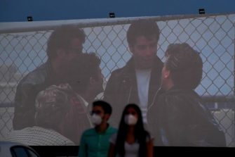 """Cinema-goers attend the screening of the US musical romantic comedy film """"Grease"""" during the reopening of the Autocine Madrid Race drive-in cinema, on May 27, 2020 in Madrid, as Spain eases lockdown measures taken to curb the spread of the COVID-19 disease caused by the novel coronavirus. - For many, it was a long-awaited chance to feel normal again, sitting in their cars belting out """"Summer Nights"""" at Madrid's drive-in cinema on a rare night out after a 10-week lockdown. (Photo by Gabriel BOUYS / AFP) (Photo by GABRIEL BOUYS/AFP via Getty Images)"""
