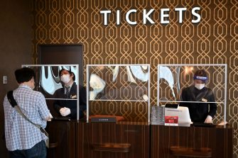 Employees wearing face shields and masks sell tickets at a cinema which is reopening following measures to curb the spread of the COVID-19 coronavirus, in Tokyo on June 5, 2020. (Photo by CHARLY TRIBALLEAU / AFP)