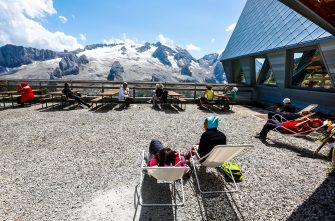 ARABBA, ITALY - JULY 20: Tourists in deck chairs taking a sunbath at the mountain station of the skiing area Porta Vescovo (2454 m ) with a panoramic view on the Marmolada glaciers in the Dolomite Alps on July 20, 2012 in Arabba, Italy. . (Photo by EyesWideOpen/Getty Images)