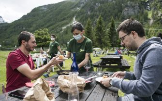 CERESOLE REALE, ITALY - JUNE 14: A waitress wears a protective mask at the mountain refuge to bring food to two men without protective mask sitting at a table near Lake Ceresole Reale inside the Gran Paradiso national park on June 14, 2020 in Ceresole Reale near Turin, Italy. The Gran Paradiso National Park is the oldest national park in Italy, located between the Valle d'Aosta and Piedmont regions, around the Gran Paradiso massif of which the main city is Ceresole Reale. Extending for an area of 71.043,79 hectares on a mainly mountainous terrain it borders on France. After the reopening of commercial activities due to the lockdown for the Coronavirus pandemic, tourism in Italy offers as an alternative to the classic tourist destinations of the beaches also the mountain areas in the Piedmont Region are many tourist areas where you can practice trekking, trekking bicycle, alpine snowboarding or just relaxing for a lunch in a refuge. Italy is returning to a more normal life from easing restrictions after a nationwide lockdown to curb the spread of Covid-19. (Photo by Stefano Guidi/Getty Images)