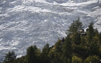 A group of people standing along the Belvedere glacier look at one of the three glaciers of the Monte Rosa (4637m) on September 26, 2015. The Belvedere Glacier is a valley glacier, mostly covered by rocks, located above Macugnaga in the region of Piedmont. The glacier lies at the base of the east face of Monte Rosa and reaches a height of about 1.800 meters above sea level at its lowest point, and lost 3,1 m of thickness of ice in the last 6 month at its lower point. AFP PHOTO / OLIVIER MORIN (Photo by Olivier MORIN / AFP)        (Photo credit should read OLIVIER MORIN/AFP via Getty Images)