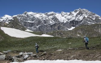CERESOLE REALE, ITALY - JUNE 14: Two people without protective masks trek on a mountain path with the background of the mountains inside the Gran Paradiso national park on June 14, 2020 in Ceresole Reale near Turin, Italy. The Gran Paradiso National Park is the oldest national park in Italy, located between the Valle d'Aosta and Piedmont regions, around the Gran Paradiso massif of which the main city is Ceresole Reale. Extending for an area of 71.043,79 hectares on a mainly mountainous terrain it borders on France. After the reopening of commercial activities due to the lockdown for the Coronavirus pandemic, tourism in Italy offers as an alternative to the classic tourist destinations of the beaches also the mountain areas in the Piedmont Region are many tourist areas where you can practice trekking, trekking bicycle, alpine snowboarding or just relaxing for a lunch in a refuge. Italy is returning to a more normal life from easing restrictions after a nationwide lockdown to curb the spread of Covid-19. (Photo by Stefano Guidi/Getty Images)