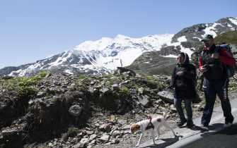 CERESOLE REALE, ITALY - JUNE 14: Two people without protective masks walk on a road with the backdrop of the mountains inside the Gran Paradiso national park on June 14, 2020 in Ceresole Reale near Turin, Italy. The Gran Paradiso National Park is the oldest national park in Italy, located between the Valle d'Aosta and Piedmont regions, around the Gran Paradiso massif of which the main city is Ceresole Reale. Extending for an area of 71.043,79 hectares on a mainly mountainous terrain it borders on France. After the reopening of commercial activities due to the lockdown for the Coronavirus pandemic, tourism in Italy offers as an alternative to the classic tourist destinations of the beaches also the mountain areas in the Piedmont Region are many tourist areas where you can practice trekking, trekking bicycle, alpine snowboarding or just relaxing for a lunch in a refuge. Italy is returning to a more normal life from easing restrictions after a nationwide lockdown to curb the spread of Covid-19. (Photo by Stefano Guidi/Getty Images)