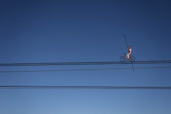 """Swiss acrobat Freddy Nock poses balancing on a bicycle on the carrying cable of a cable car during the """"Glacier 3000"""" Air show, an event marking the reopening of the Alpine facilities on June 23, 2020 above Les Diablerets following the lockdown due to the COVID-19 outbreak, caused by the novel coronavirus. (Photo by Fabrice COFFRINI / AFP) (Photo by FABRICE COFFRINI/AFP via Getty Images)"""