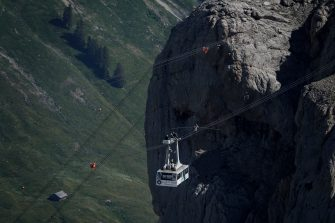 """Swiss acrobat Freddy Nock balances on a bicycle on the carrying cable of a cable carduring the """"Glacier 3000"""" Air show, an event marking the reopening of the Alpine facilities on June 23, 2020 above Les Diablerets following the lockdown due to the COVID-19 outbreak, caused by the novel coronavirus. (Photo by Fabrice COFFRINI / AFP) (Photo by FABRICE COFFRINI/AFP via Getty Images)"""