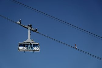 """Swiss acrobat Freddy Nock balances blindfolded on the carrying cable of a cable car during the """"Glacier 3000"""" Air show, an event marking the reopening of the Alpine facilities on June 23, 2020 above Les Diablerets following the lockdown due to the COVID-19 outbreak, caused by the novel coronavirus. (Photo by Fabrice COFFRINI / AFP) (Photo by FABRICE COFFRINI/AFP via Getty Images)"""