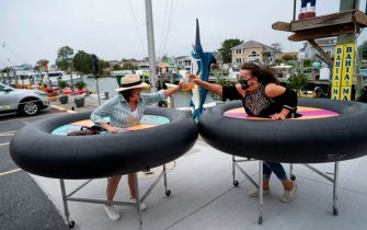 Restaurant guests try out social distancing devices made of rubber tubing as Fish Tails bar and grill opens for in person dining during the Coronavirus pandemic on May 29, 2020 in Ocean City, Maryland. - At 5pm today, restaurants and bars in the state of Maryland can open for outdoor and open air dining. (Photo by Alex Edelman / AFP) (Photo by ALEX EDELMAN/AFP via Getty Images)