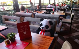 "Plush toy pandas are placed at tables with a card reading ""Leave this place empty for your health"" for the social distancing of customers in a restaurant in the Sogutozu district in Ankara, on July 1, 2020, as part precautionary measures amid the COVID-19 (novel coronavirus) pandemic. (Photo by Adem ALTAN / AFP) (Photo by ADEM ALTAN/AFP via Getty Images)"