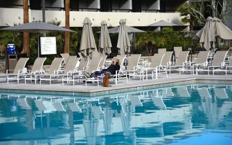 PALM SPRINGS, CALIFORNIA - FEBRUARY 28, 2019: A tourist lounges with her pet dog beside a hotel swimming pool in Palm Springs, California. (Photo by Robert Alexander/Getty Images)
