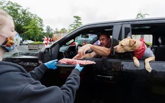 """VANCOUVER, BRITISH COLUMBIA - JULY 01: Attendees pick up food following an indoor """"reverse"""" parade for Canada Day at PNE on July 01, 2020 in Vancouver, British Columbia.The Canada Day parade was organized as a socially distanced event to allow spectators to remain in cars while driving by as entertainers perform.  (Photo by Andrew Chin/Getty Images)"""