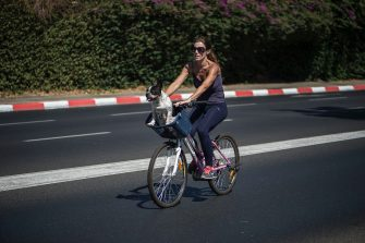 TEL AVIV, ISRAEL - OCTOBER 04:  A woman rides her bicycle with her pet dog in the middle of the empty streets of Tel Aviv during Yom Kippur on October 04, 2014 in Tel Aviv, Israel. Israel comes to a standstill for 25-hours during the high holiday of Yom Kippur, the day of atonement and the holiest of Jewish holidays when observant Jews fast and Israelis are prohibited from driving.  (Photo by Ilia Yefimovich/Getty Images)