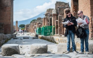 POMPEI, ITALY - APRIL 12:  Tourists look at their maps as they visit the archaeological site on April 12, 2014 in Pompei, Italy.  The Italian government has enacted a series of provisions for the strengthening of the private security inside the archaeological site, following the recent theft of part of the fresco of Artemis. In 2013 Pompeii was visited by almost 2.5 million tourists.  (Photo by Giorgio Cosulich/Getty Images)